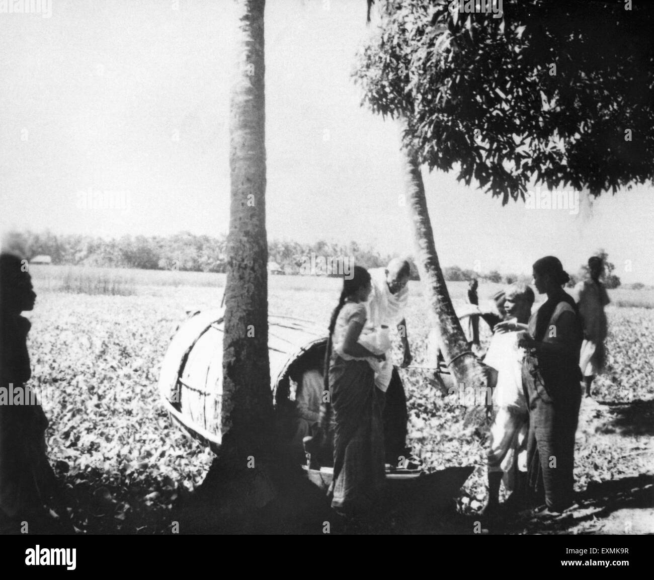 Mahatma Gandhi ; accompanied by Abha Gandhi leaving a boat during his visit in the riot effected area of Noakhali - Stock Image