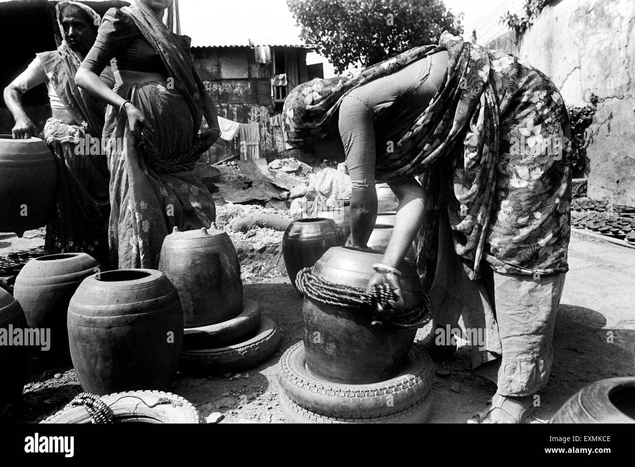 Women give finishing touches to earthenware baked clay vessels at Kumbhaewada ; Dharavi Mumbai - Stock Image