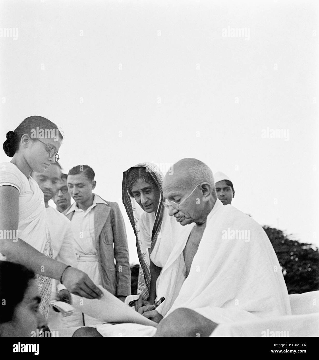 After prayer Mahatma Gandhi gives an autograph in Pune ; 2nd Oct 1944 ; Abha Gandhi ; Rajkumari Amrit Kaur NO MR - Stock Image