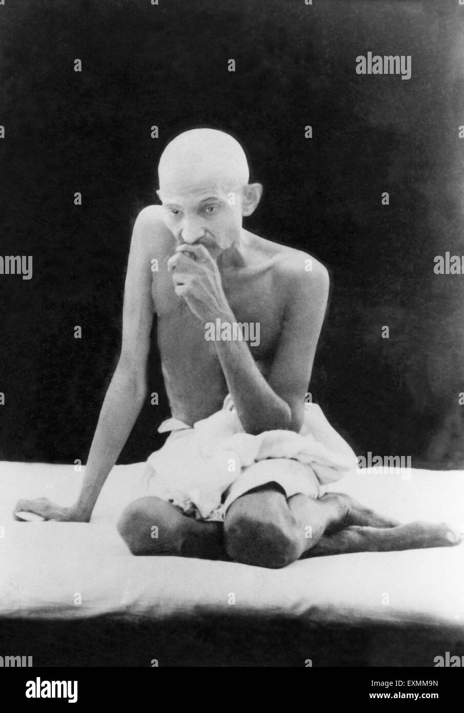 Mahatma Gandhi ; with shaved head in characteristic pose ; India NO MR - Stock Image