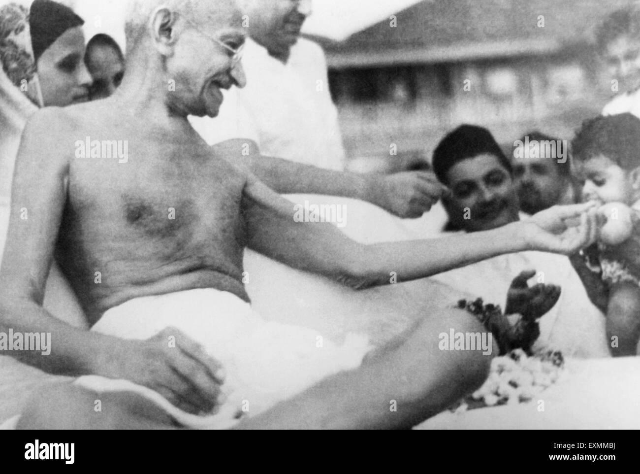 Mahatma Gandhi ; distributing fruits to children at Juhu Beach bombay india May 1944 - Stock Image