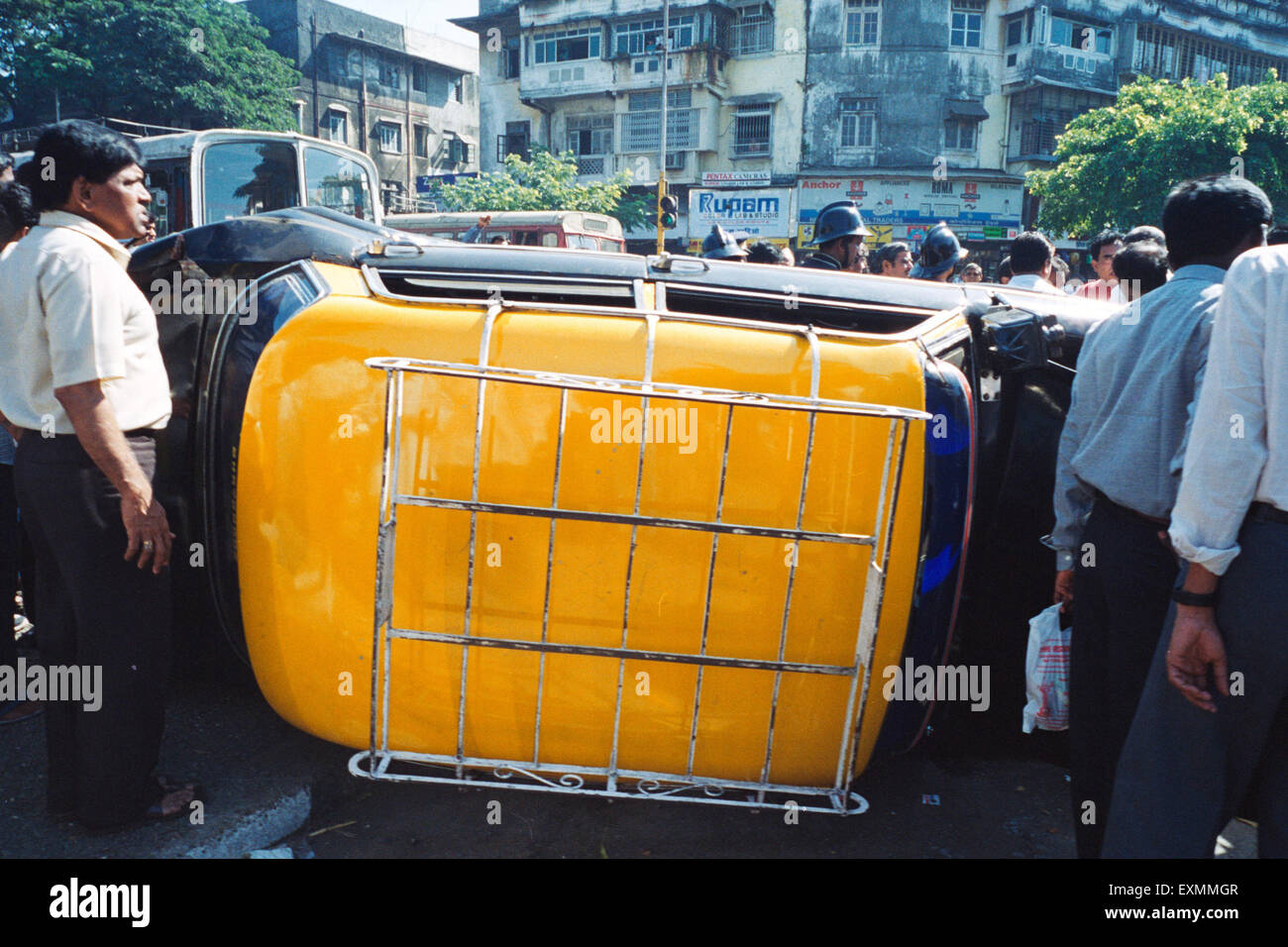 Road accident black yellow taxi turned turtle Kings circle Bombay Mumbai Maharashtra India - Stock Image