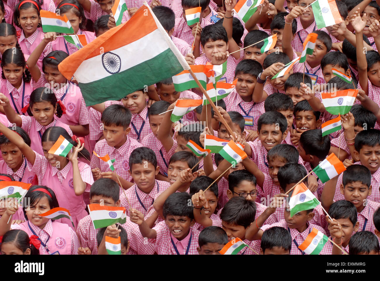 School children celebrate Indian Independence Day by waving Indian tri color flag in Bombay Mumbai ; Maharashtra - Stock Image