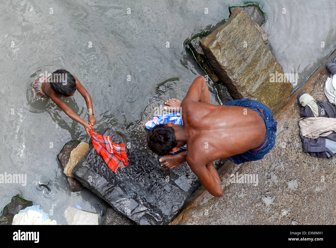 A washer man wash clothes with his young child in dirty waters at Dharavi in Bombay now Mumbai ; Maharashtra ; India - Stock Image