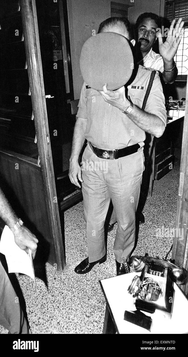 police officer covering face with hat mumbai Maharashtra India - Stock Image