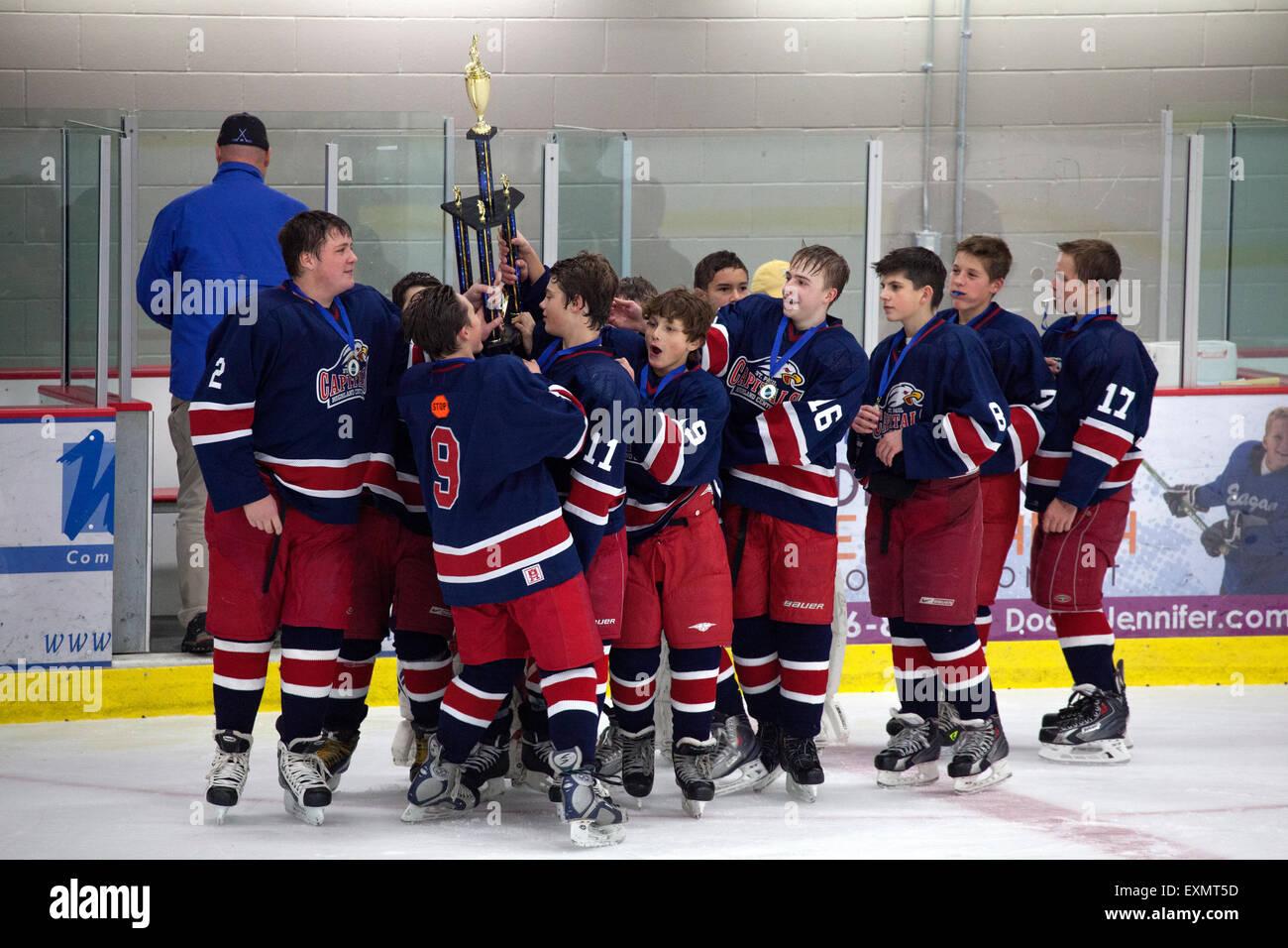 Young teen boys holding up hockey tournament winning trophy. Stillwater Minnesota MN USA - Stock Image