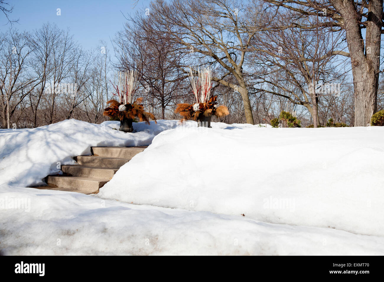 Two pots decorating a winter walkway filled with evergreen bows berry branches and leaves. Minneapolis Minnesota - Stock Image