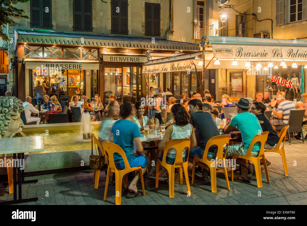 Night view of a Brasserie cafe restaurant with people seated outside at tables, Carpentras, Provence, France - Stock Image
