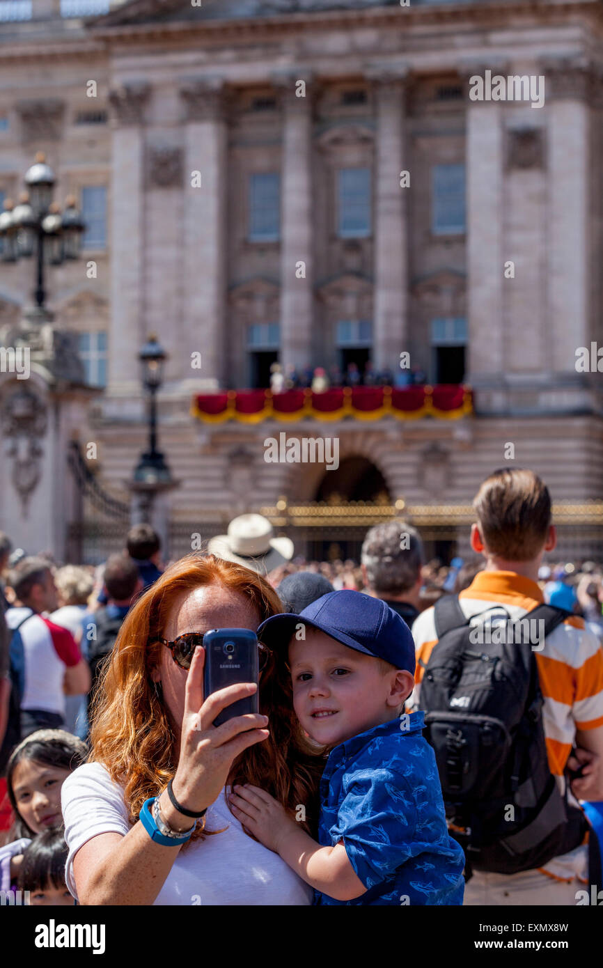 A Visitor Takes A Selfie Of Herself and Child Outside Buckingham Palace, London, England - Stock Image