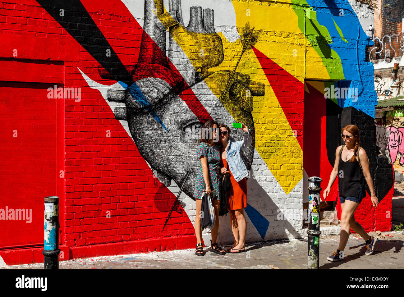 Young Women Pose For A selfie In Front Of Some Street Art/Graffiti, Brick Lane, London, England - Stock Image