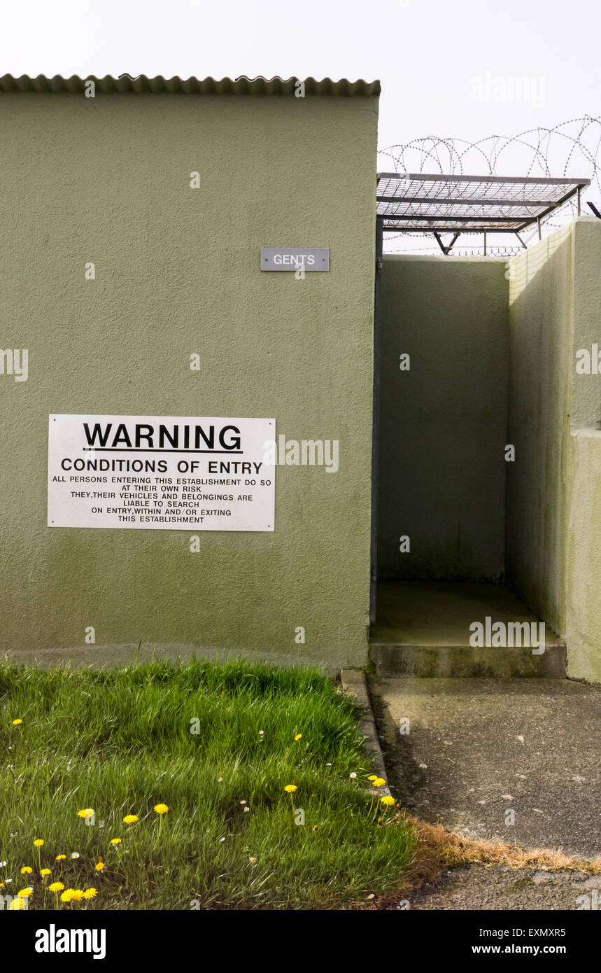 Culdrose, Cornwall, England. Gents toilet with warning sign: conditions of entry... - Stock Image