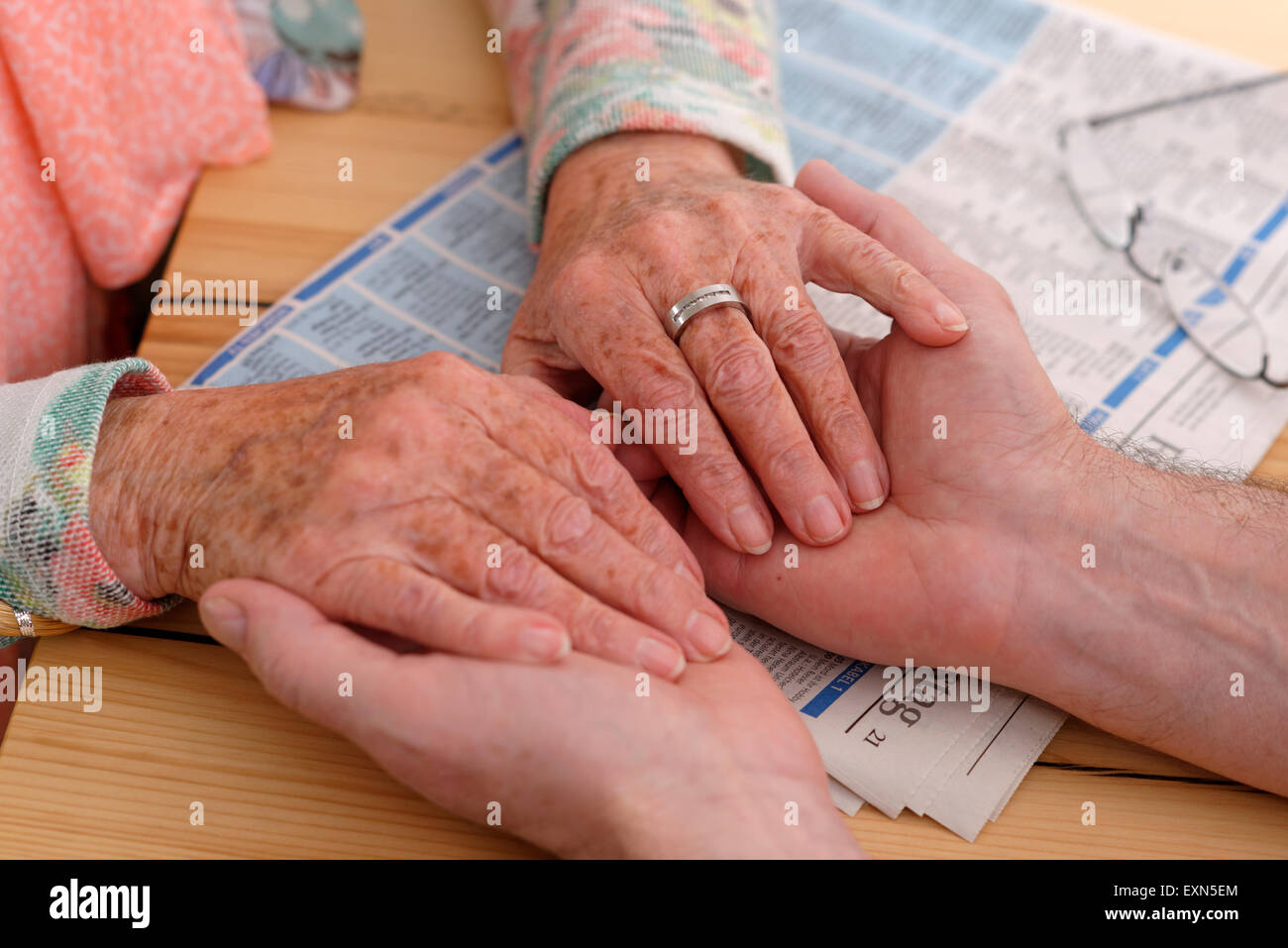 Hands of senior woman holding man's hands - Stock Image