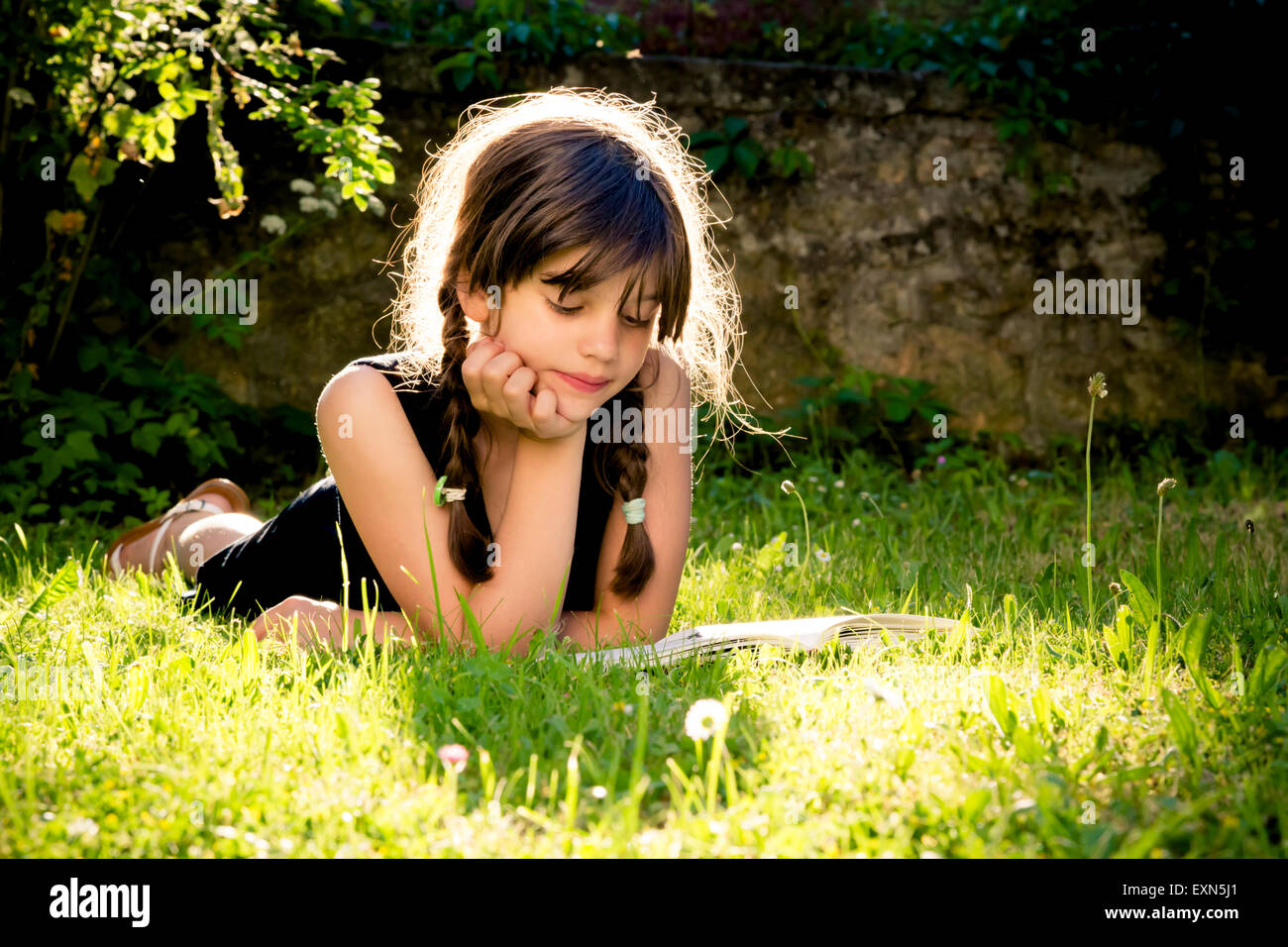 Girl lying on a meadow reading a book - Stock Image