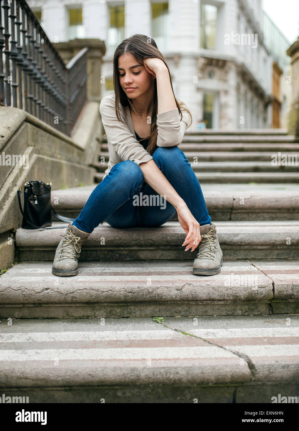 Spain, Oviedo, young woman sitting on stairs in the old town - Stock Image