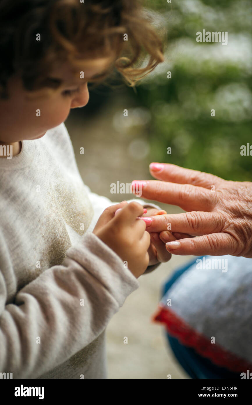 Little girl painting her grandmother's finger nails - Stock Image