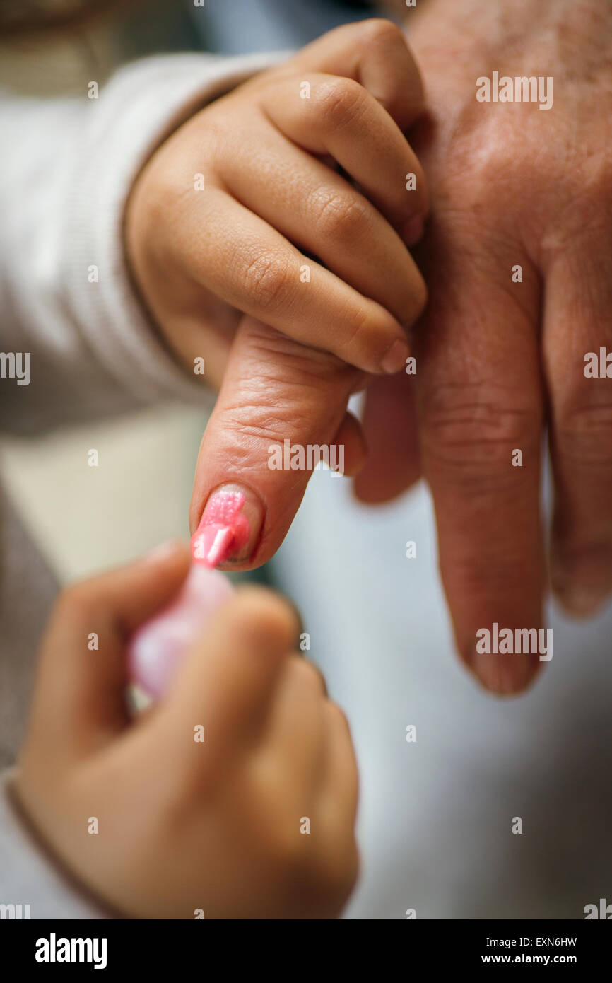 Little girl painting her grandmother's finger nails - Stock Image