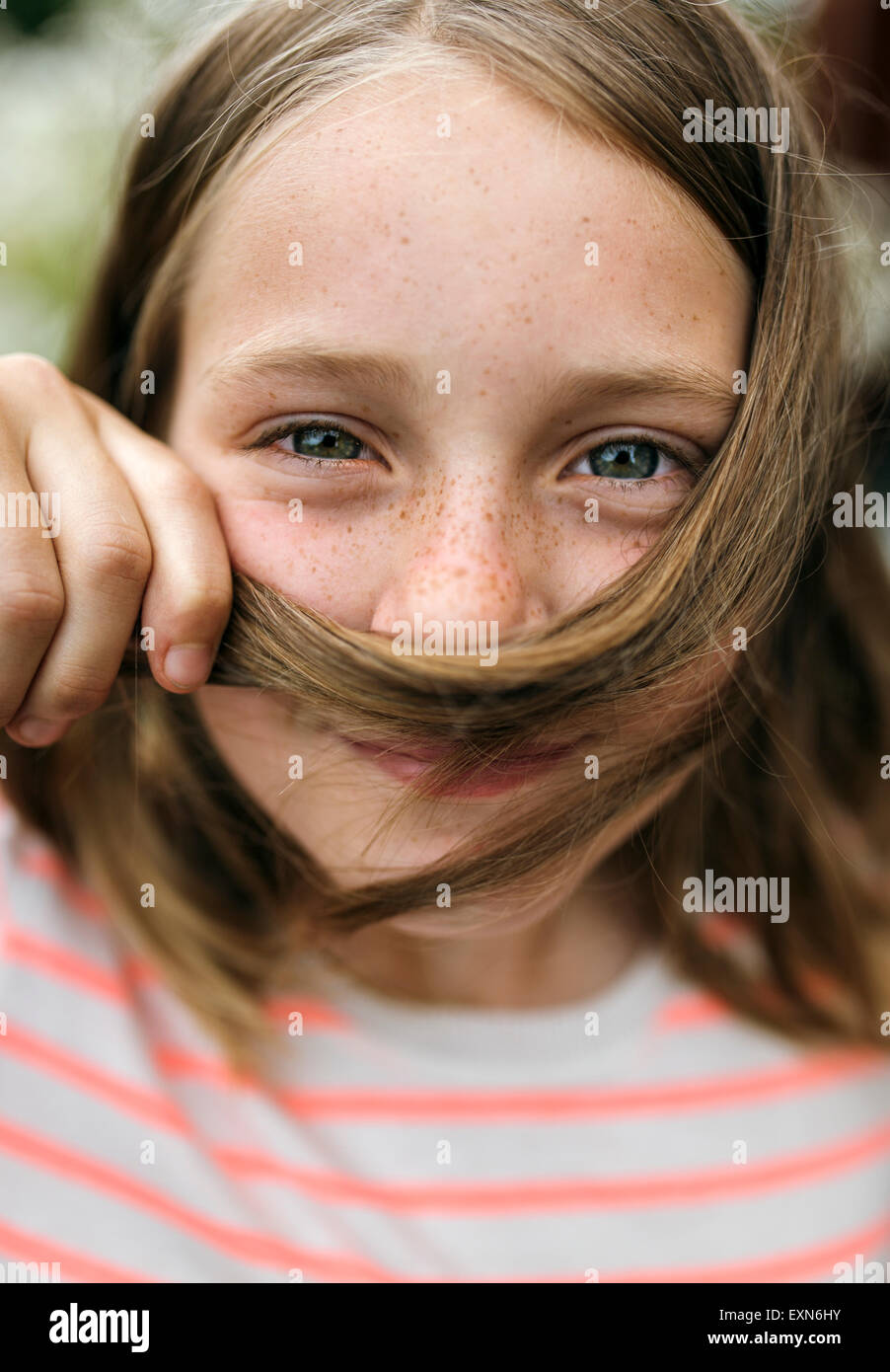 Portrait of smiling girl holding strand of hair under her nose - Stock Image
