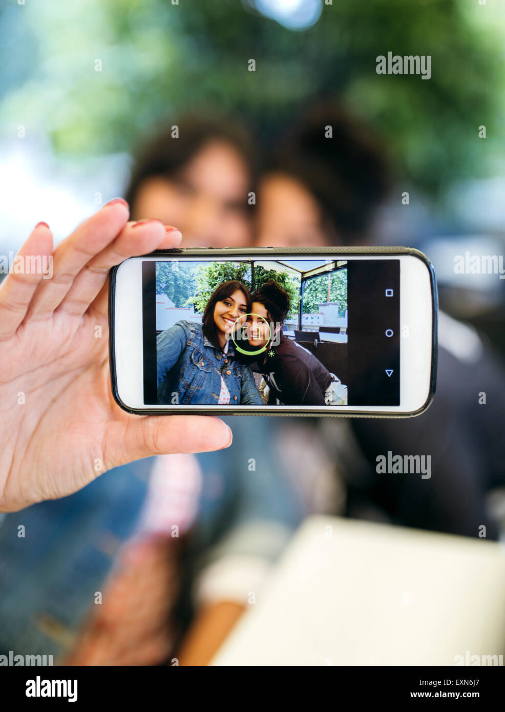 Display of smartphone with photography of two women taking a selfie - Stock Image
