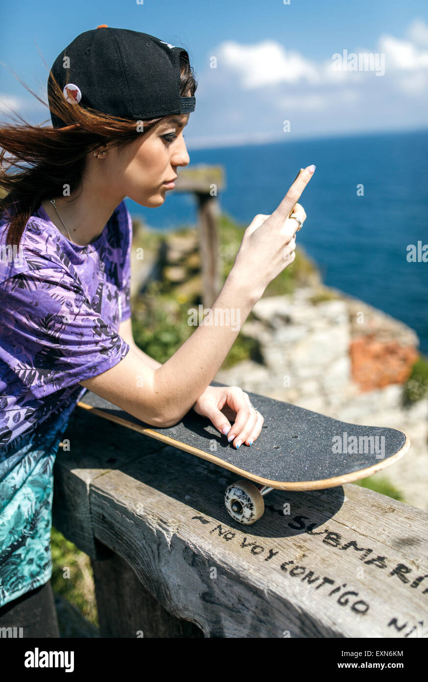 Spain, Gijon, female skate boarder reading text message - Stock Image