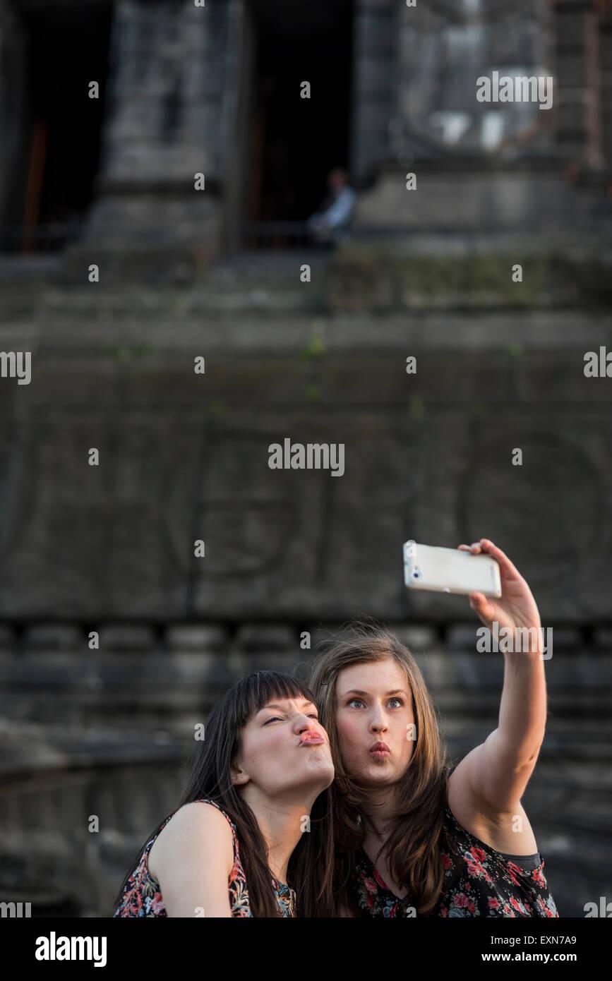 Germany, Koblenz, Deutsches Eck, playful tourists taking selfie at Emperor-Wilhelm monument - Stock Image