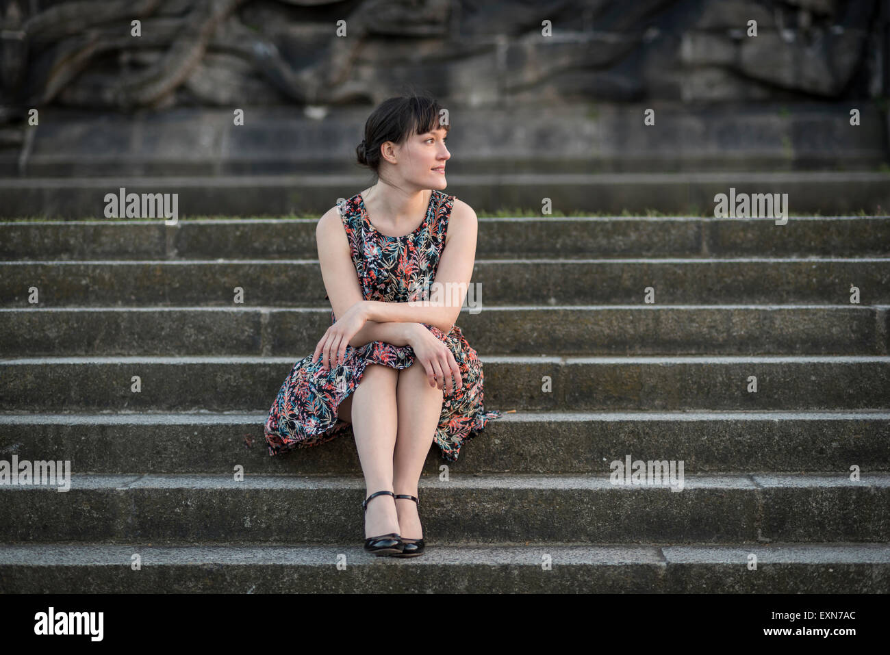 Germany, Koblenz, Deutsches Eck, young woman sitting on stairs - Stock Image