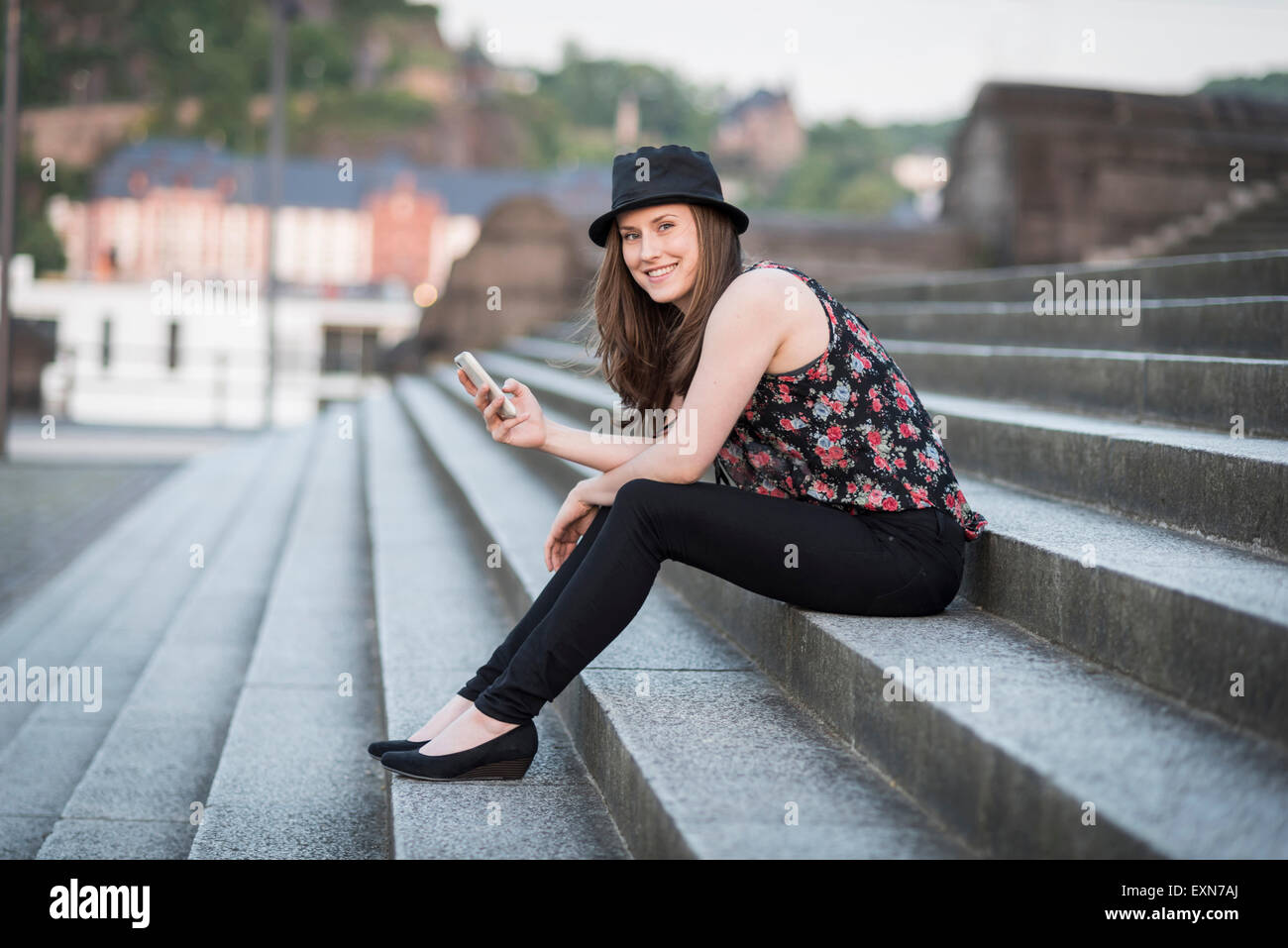 Germany, Koblenz, Deutsches Eck, young woman with cell phone sitting on stairs - Stock Image