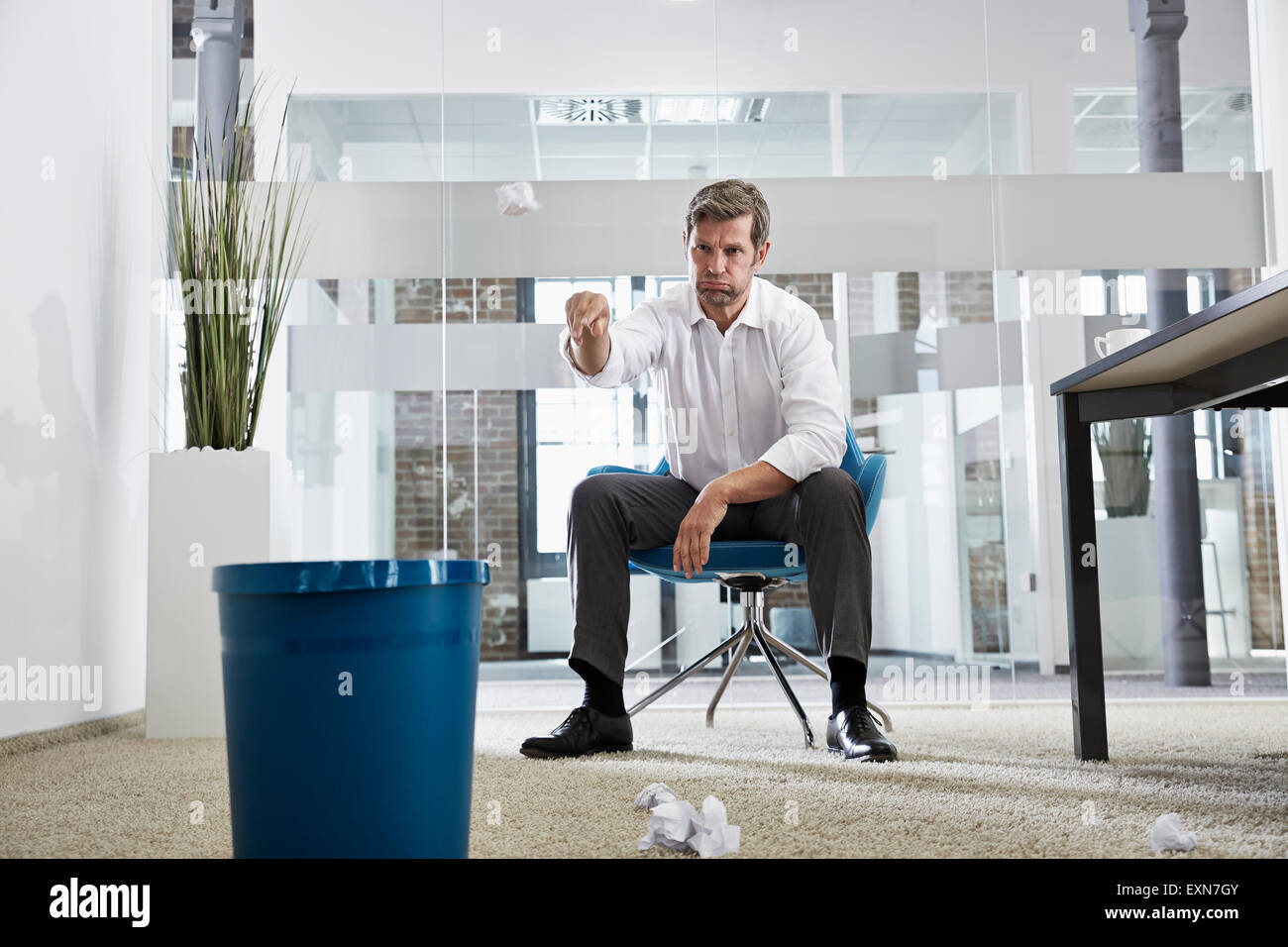 Businessman In Office Throwing Crumpled Paper In Wastepaper Basket   Stock  Image