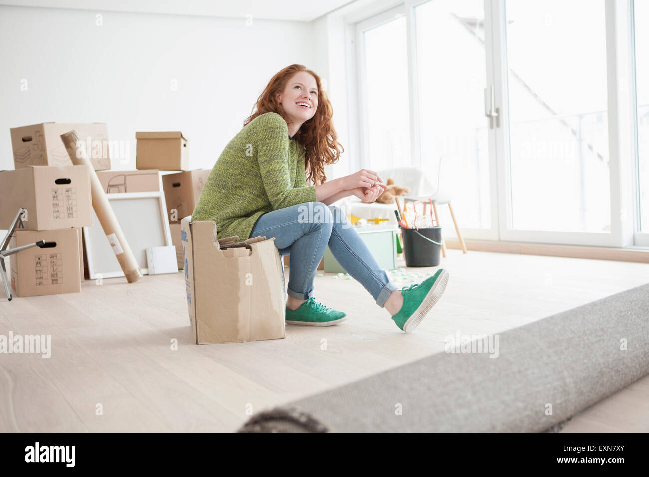 Young woman in new flat sitting on cardboard box - Stock Image
