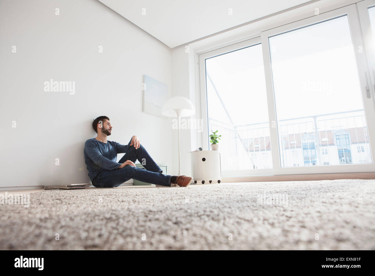 Young man sitting on the floor of living room looking through window - Stock Image
