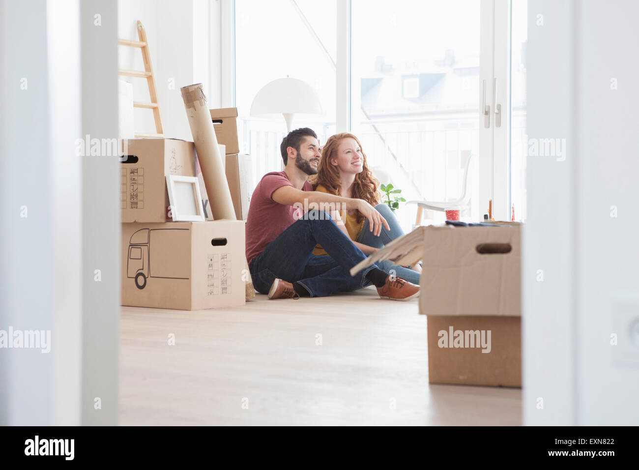 Young couple in new flat with cardboard boxes - Stock Image
