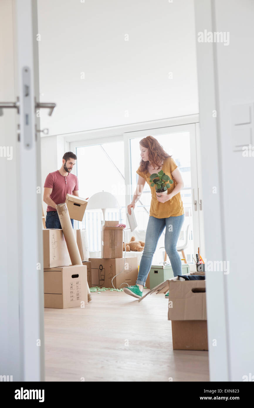 Young couple in new flat unpacking cardboard boxes - Stock Image