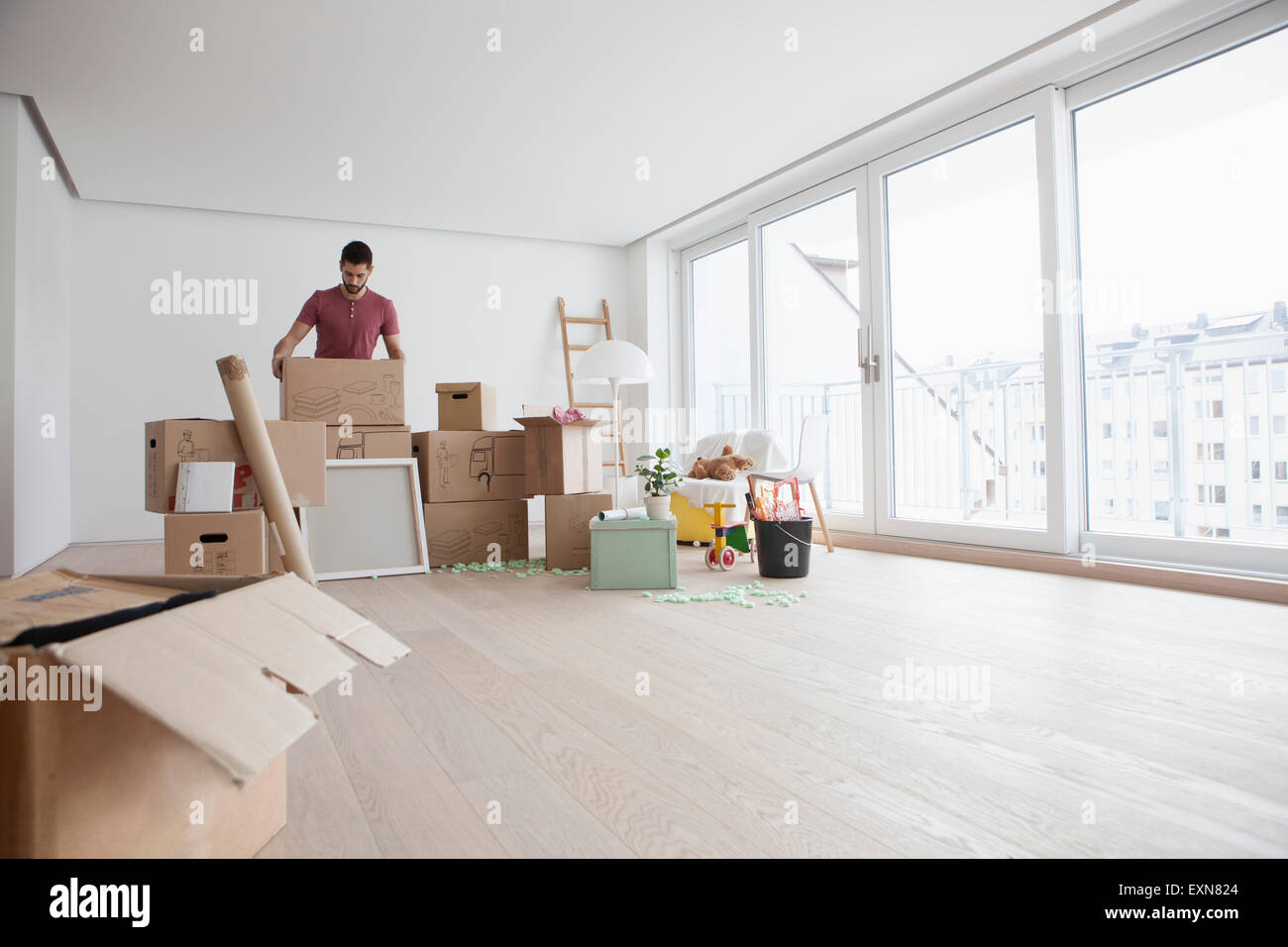 Young man in new flat unpacking cardboard boxes - Stock Image