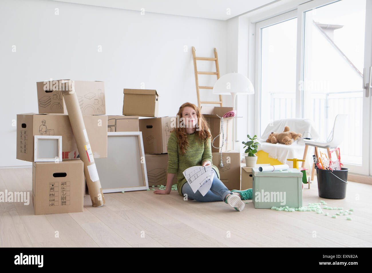 Young woman in new flat with cardboard boxes holding ground plan - Stock Image