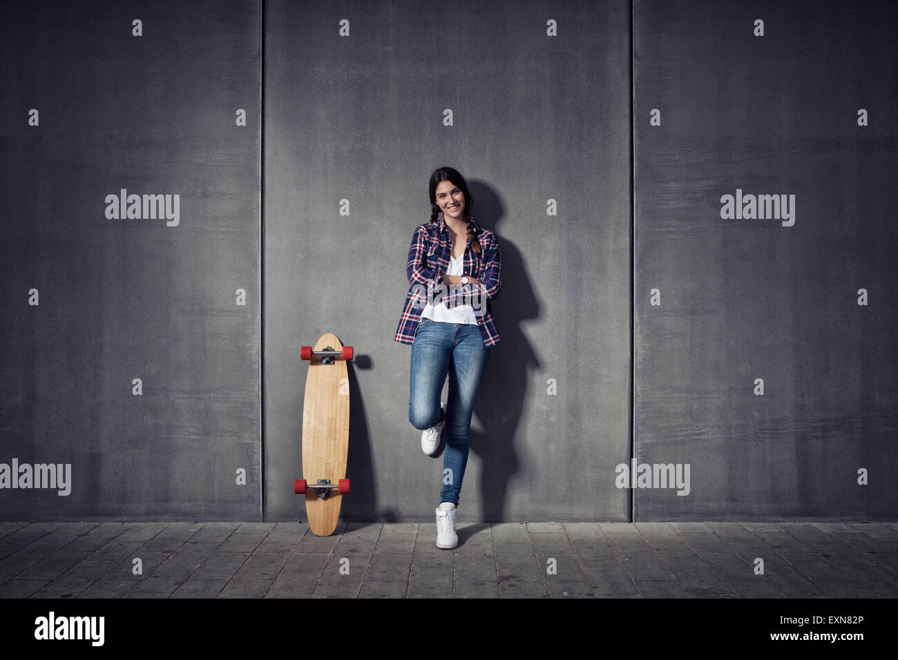 Young woman standing besides her longboard - Stock Image
