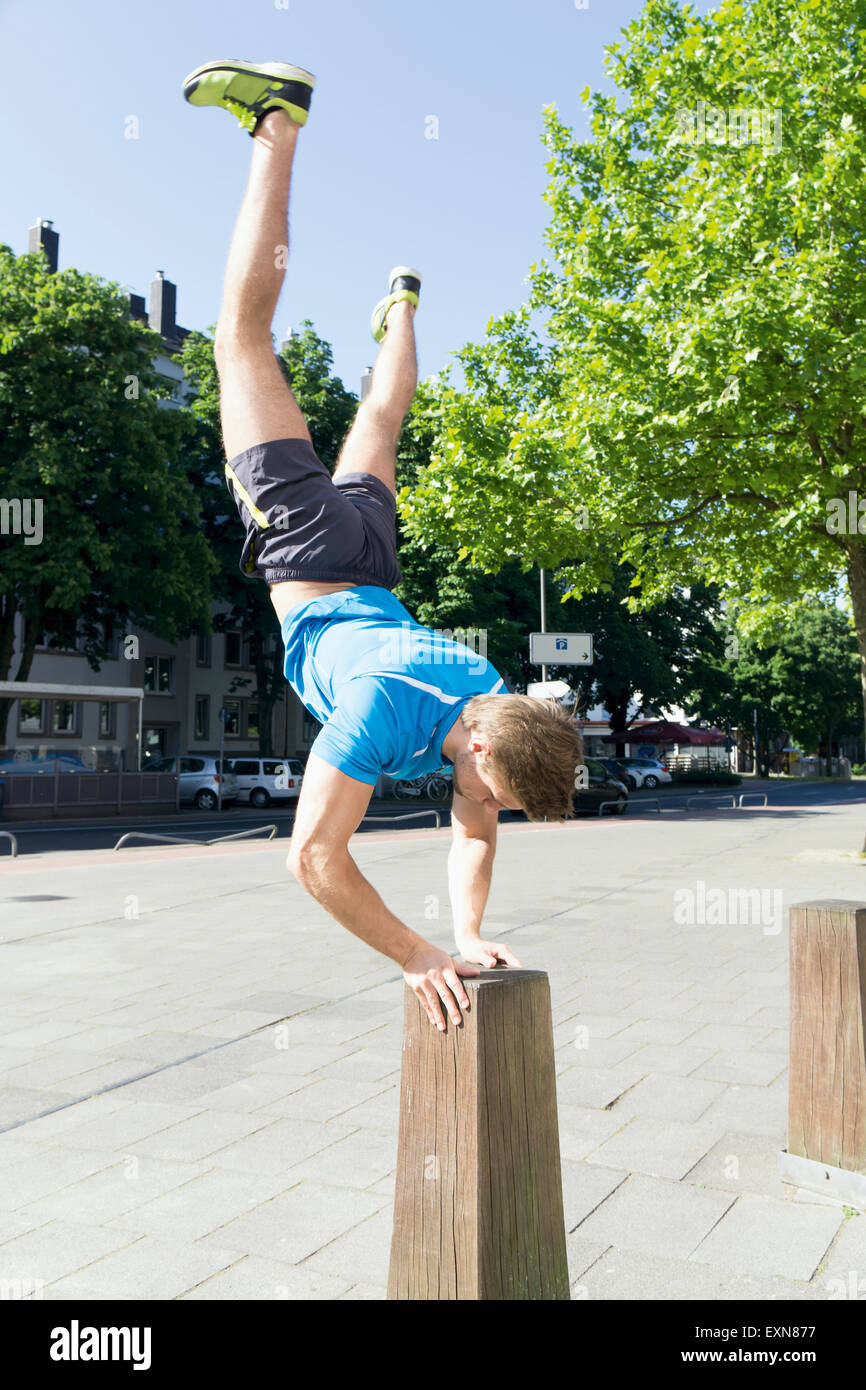 Athlete doing a handstand on a bollard - Stock Image