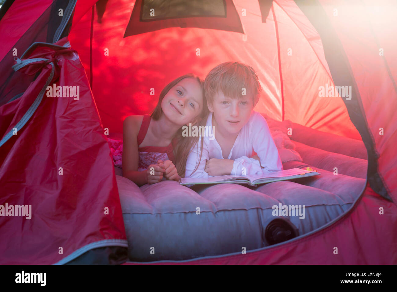 Portrait of brother and sister lying in a red tent with a book - Stock Image
