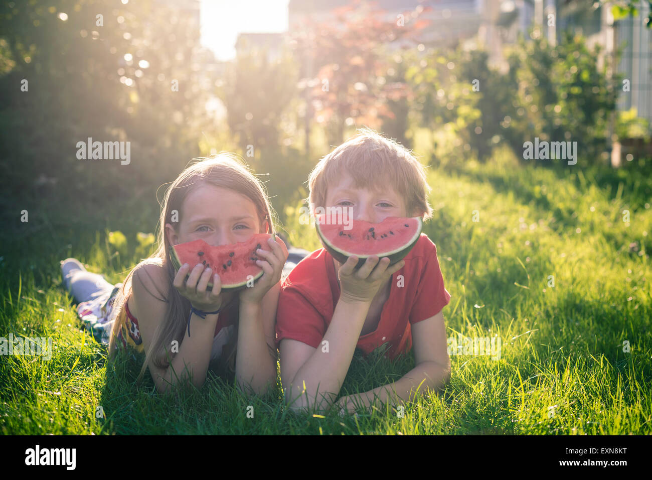 Boy and girl lying on a meadow covering part of her face with slice of watermelon - Stock Image
