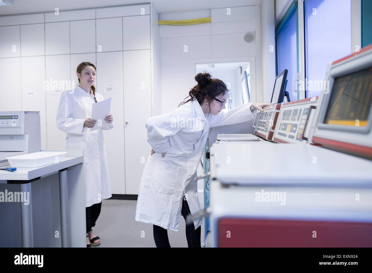 Laboratory assistant checking laboratory device - Stock Image