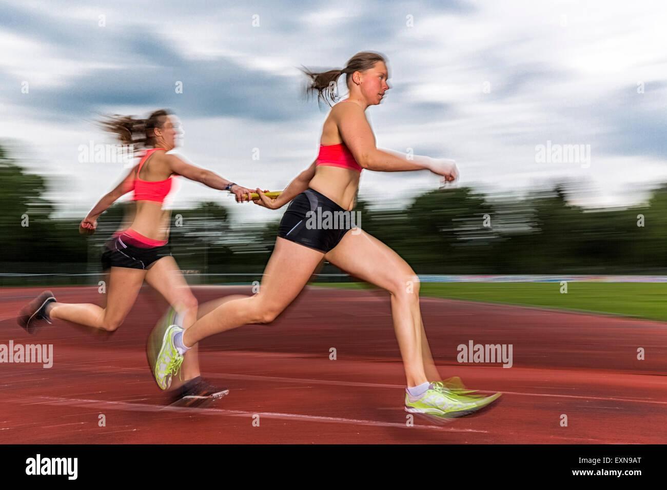 Two sprinters passing the baton - Stock Image