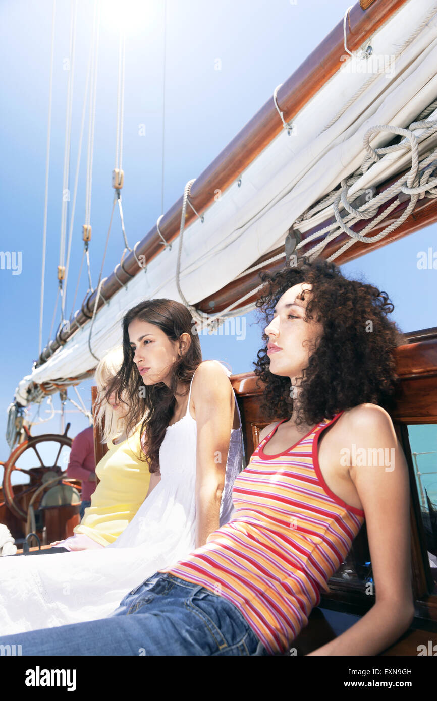 Three relaxed young women on a sailing ship - Stock Image