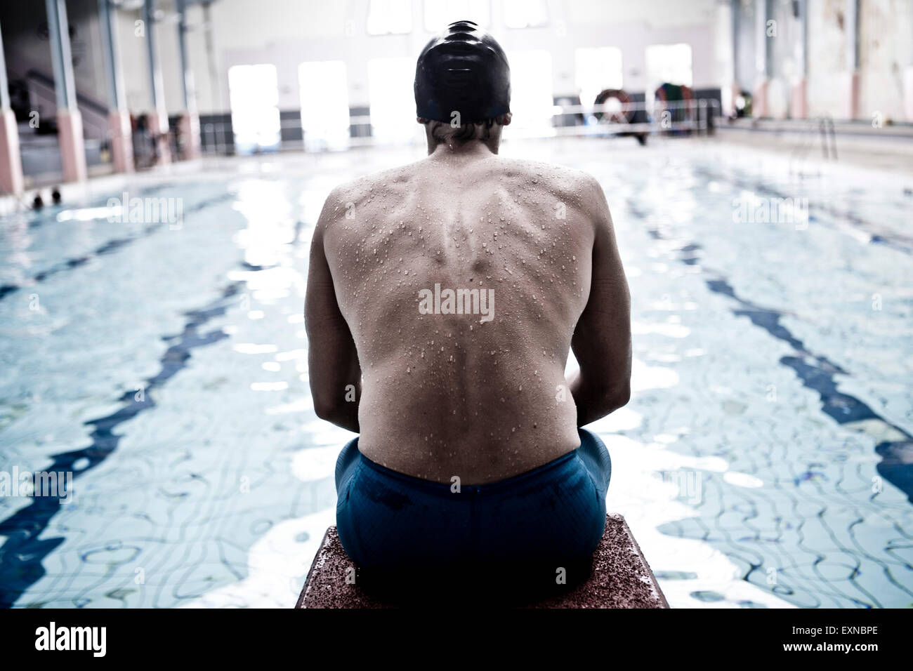 Swimmer in indoor pool sitting on starting block - Stock Image