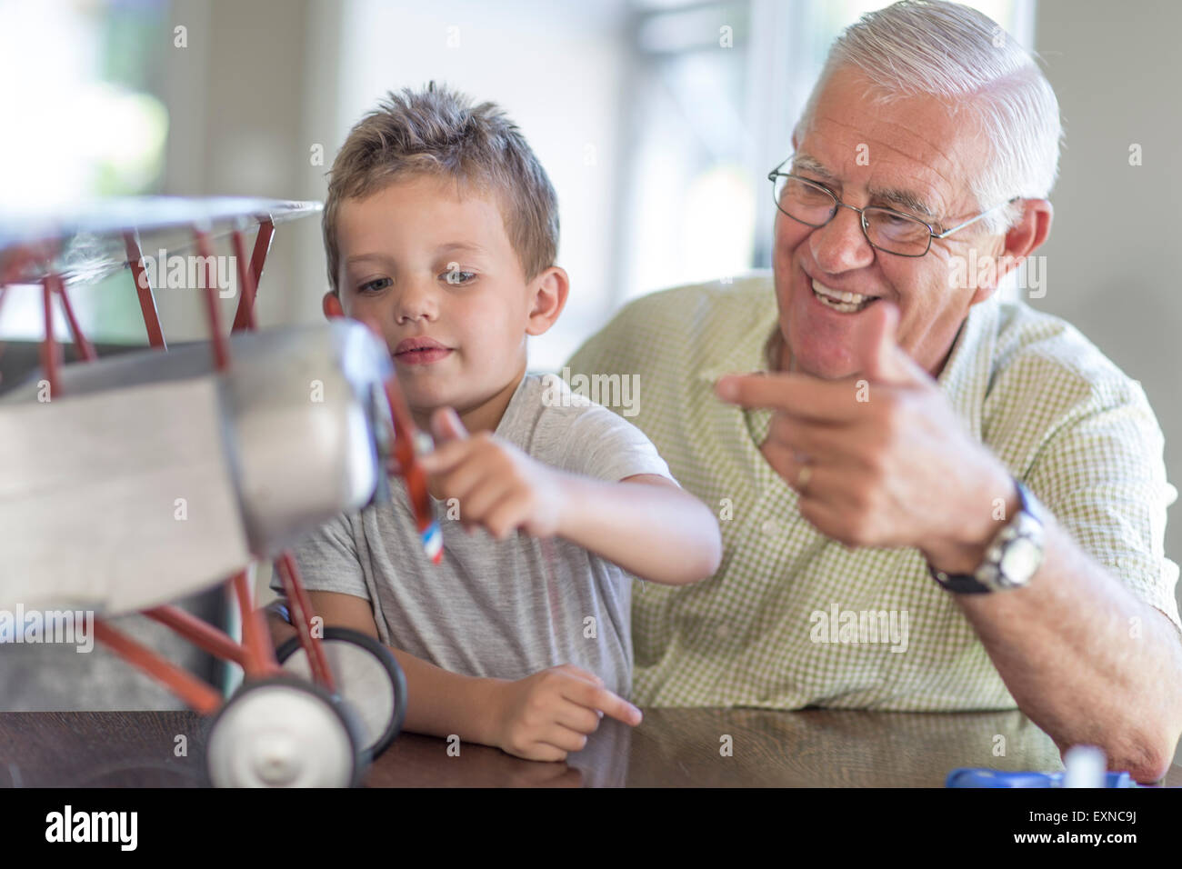 Grandfather and grandson building up a model airplane - Stock Image