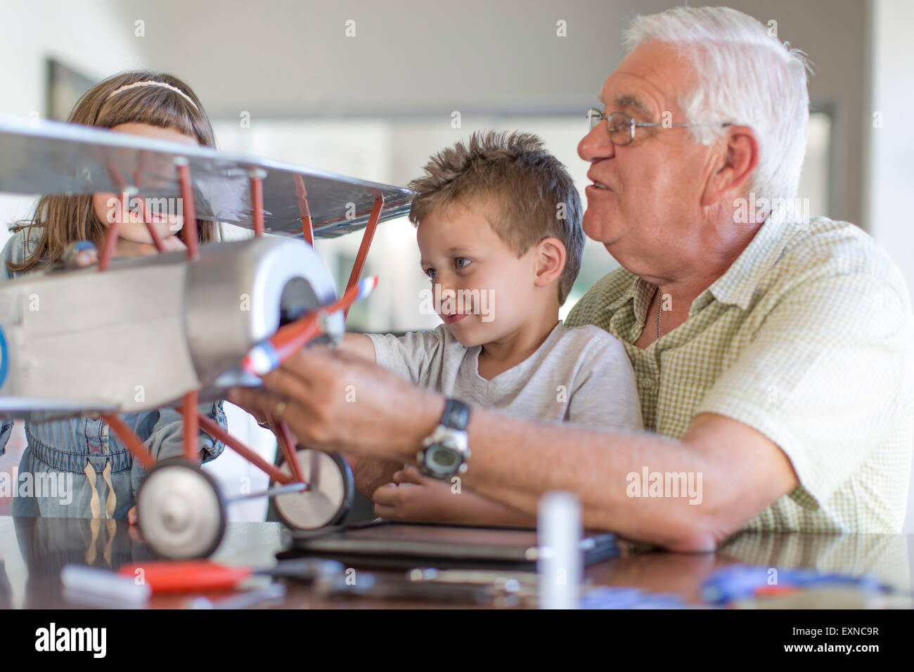 Grandfather and grandchildren building up a model airplane - Stock Image