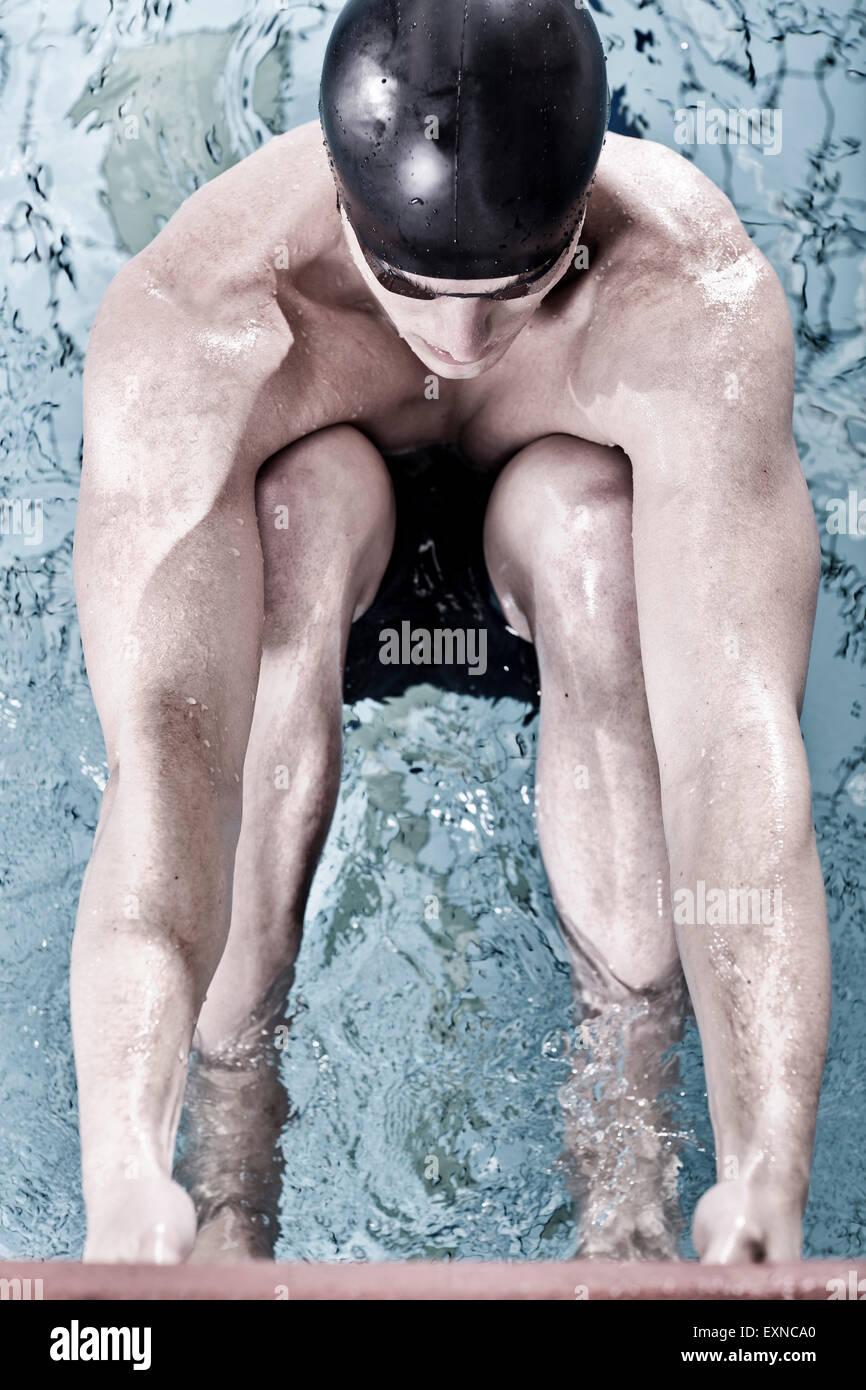 Backstroke swimmer in indoor pool in starting position - Stock Image
