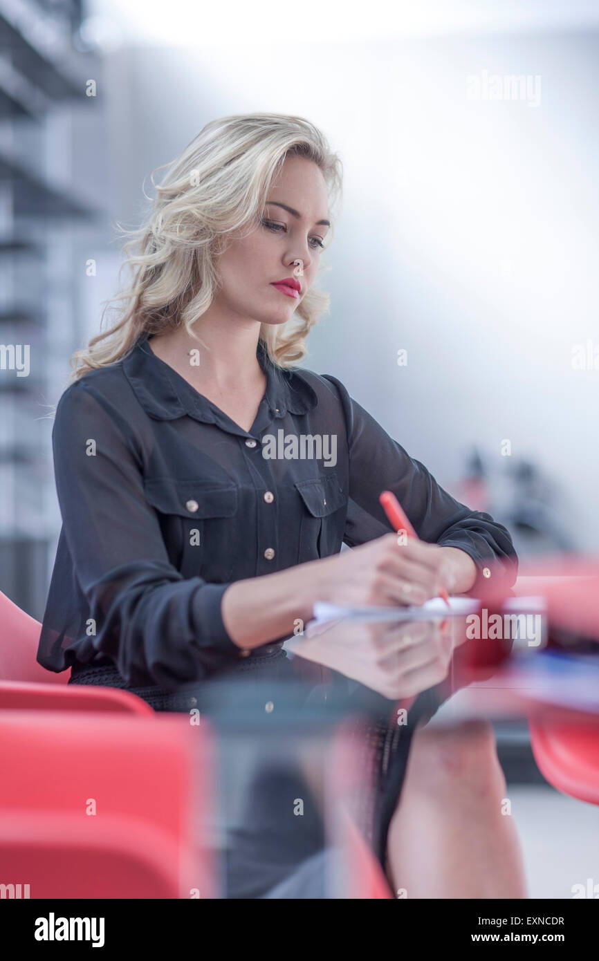 Businesswoman writing something at desk - Stock Image