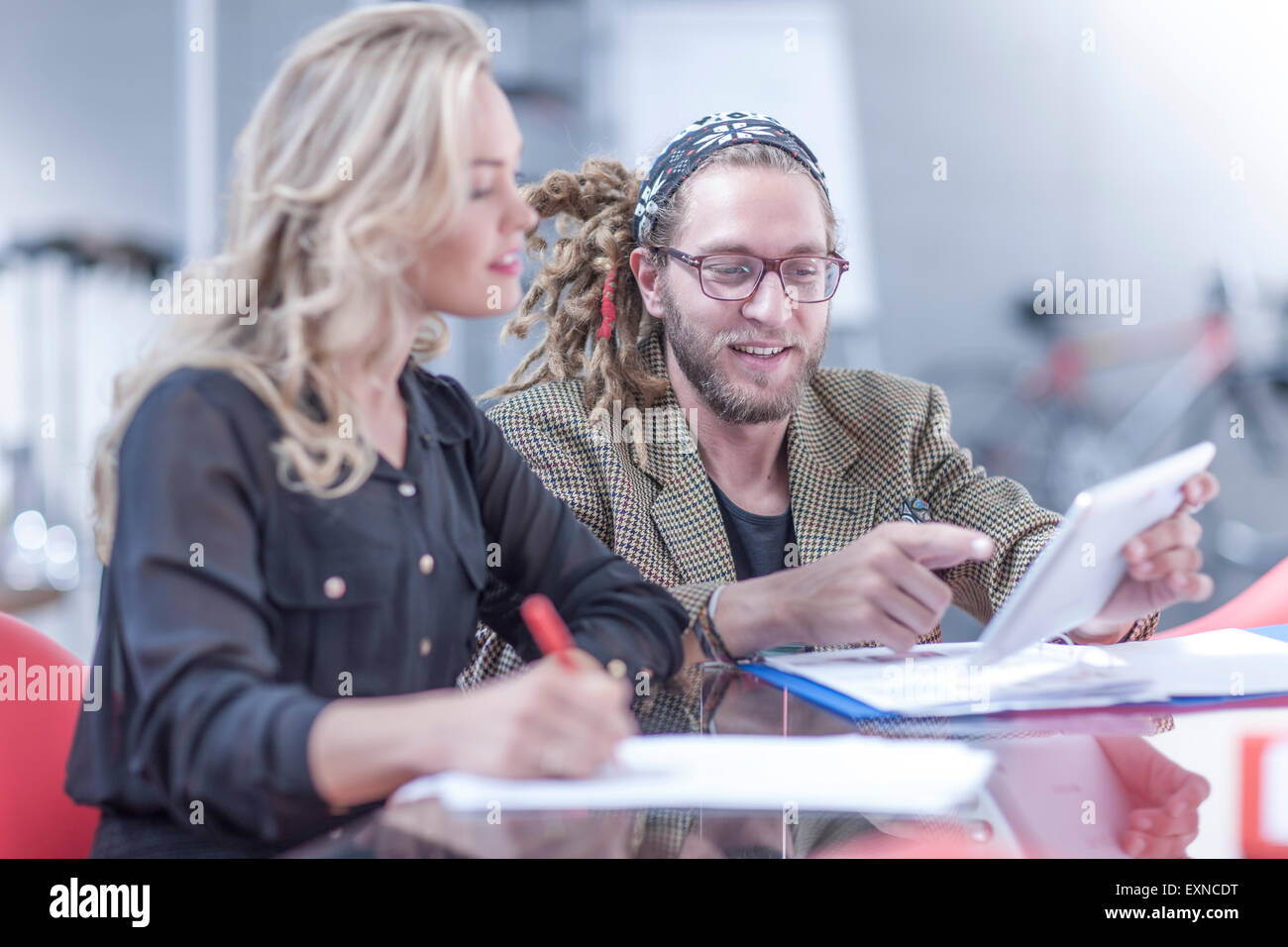 Portrait of a man showing his colleague something on mini tablet - Stock Image