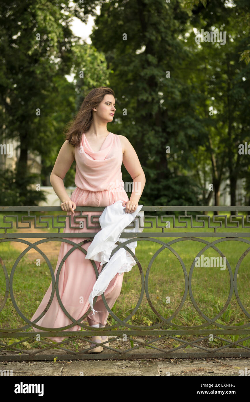 young romantic woman in a light pink tunic in a park - Stock Image
