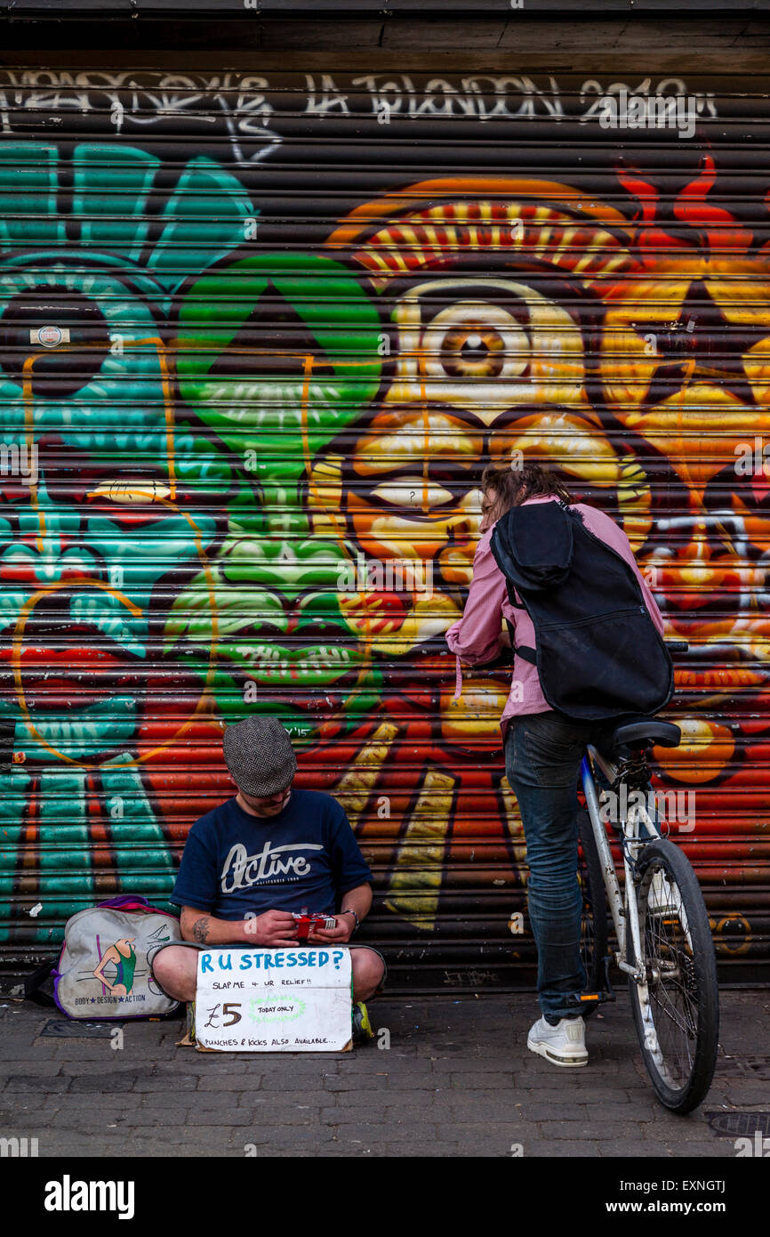 A Man Sits With A Sign Offering People The Chance to De-Stress By Slapping Him and Paying £5, Brick Lane, London, - Stock Image