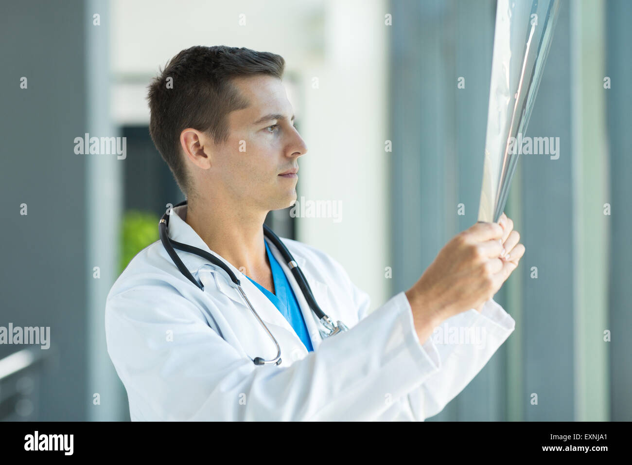 young doctor studying patient's x ray at hospital - Stock Image