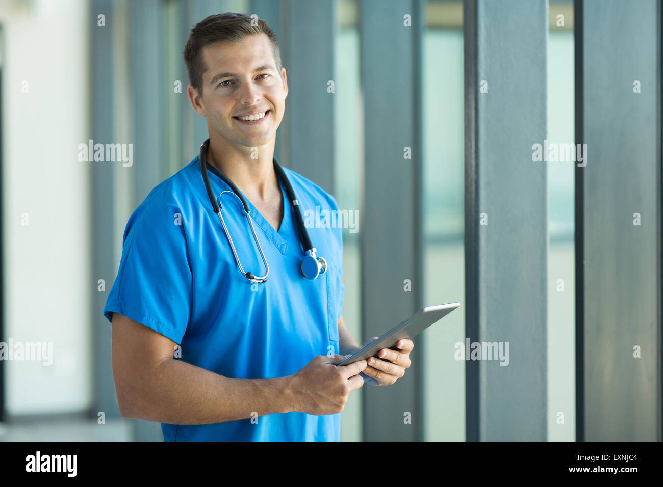 cheerful young nurse with tablet pc in office - Stock Image